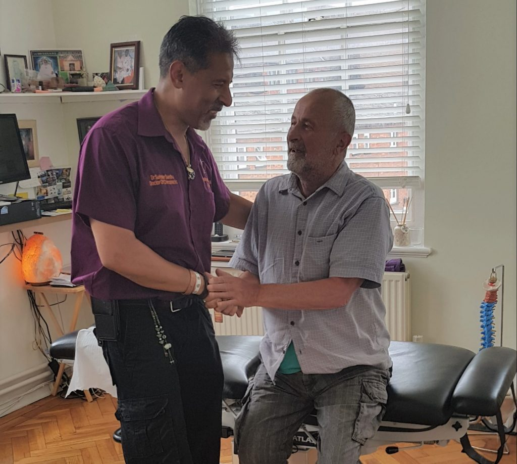 surinder sandhu treating elderly patient at the bedford chiropractic clinic - treat dad to chiropractic