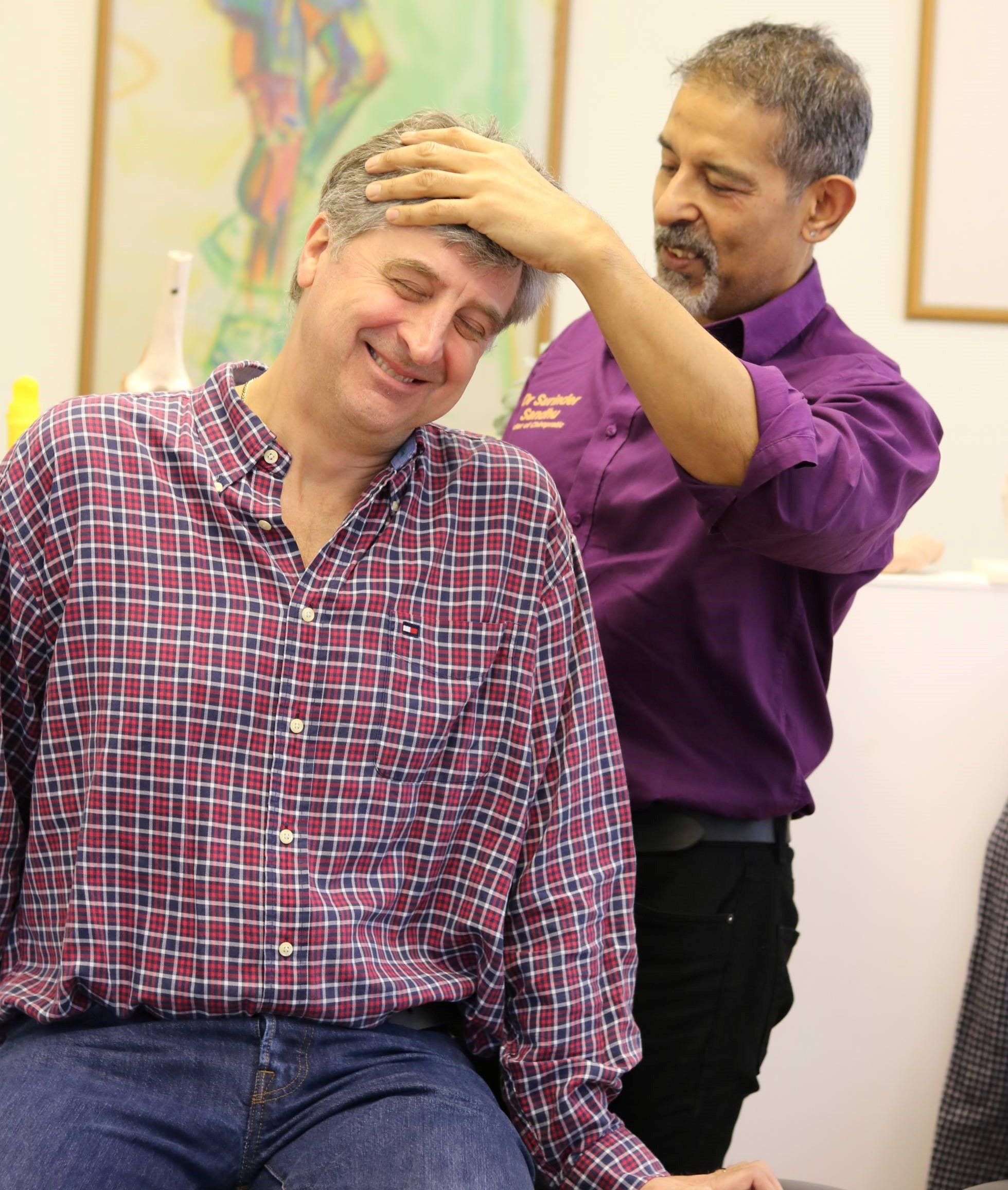 Older man smiling whilst receiving chiropractic treatment for neck pain