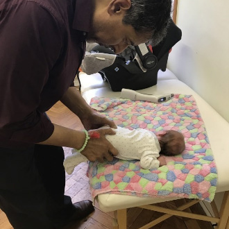 Surinder Sandhu working on a newborn baby