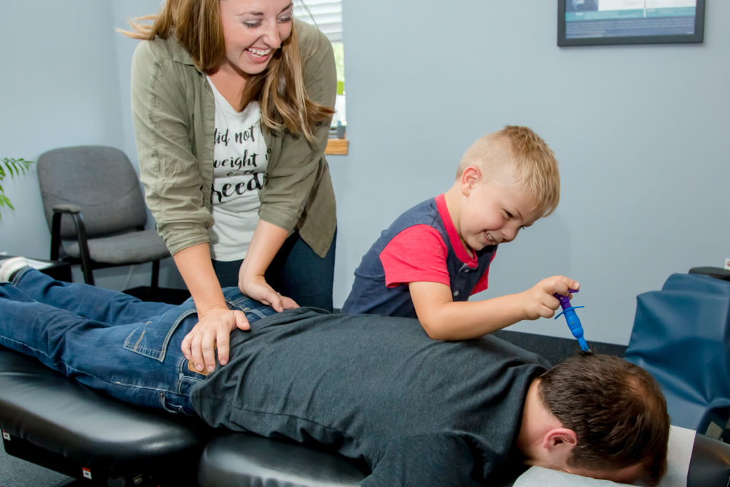 child and mother treating dad to chiropractic