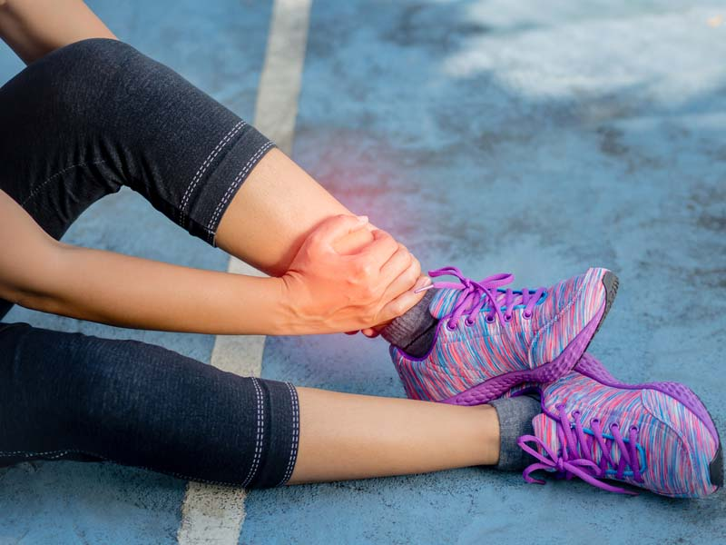woman athlete or runner experiencing ankle pain
