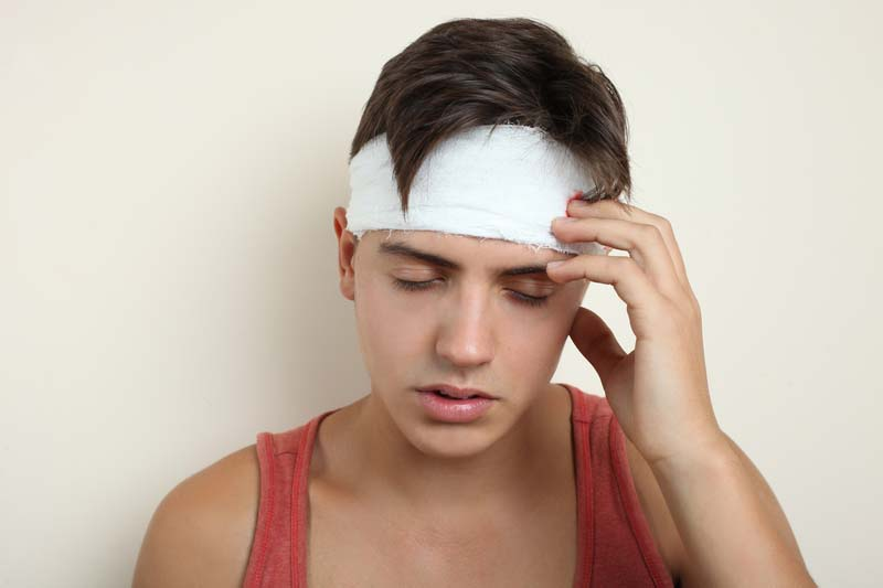 young boy suffering with a head injury