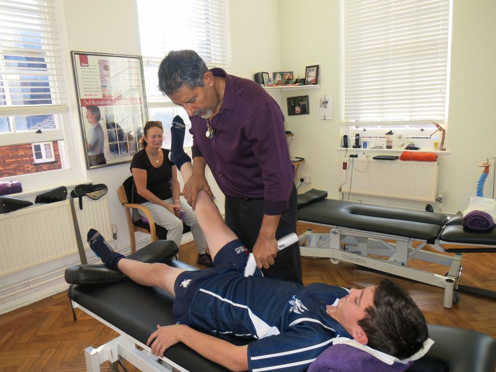 Young boy who does sports receiving chiropractic treatment from surinder sandhu at the bedford chiropractic clinic
