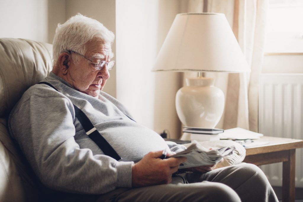 senior man reading newspaper inactive lifestyle by sitting