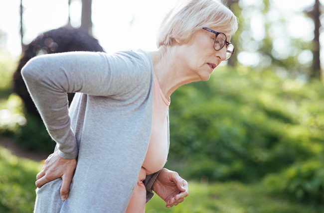 older woman walking outdoors with back pain