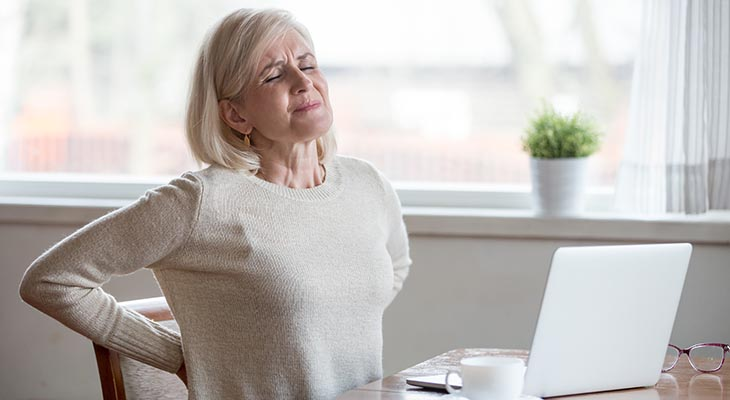 older woman with back pain sitting whilst working from home